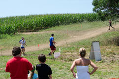 Race through corn fields. People race in and out of corn fields at the 2012 mudathlon in Indiana, as spectators look on Stock Photography