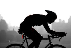 Race Day. Cyclist with red tail light, against a rural backdrop Stock Photography