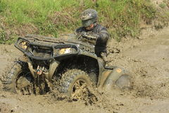 Race four-wheeler driver in puddle of mud Stock Photo