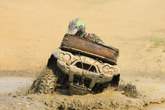 Race four-wheeler in a puddle of mud Stock Photos