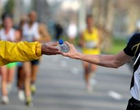 Race Refreshment. Runner take a bottle of water on a long distance race Stock Image