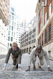Race Start in City. Two businessmen in the ready position to start a race in the financial distric Stock Photos