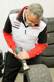 Race tires. THRUXTON, UNITED KINGDOM - MAY 1, 2011: Honda Racing mechanic removing blisters with a hot iron on race tires for his team in the British Touring Car Royalty Free Stock Image