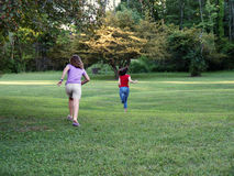 Race to the tree. Teen sisters racing to a distant tree stock photos