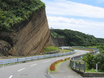 Race track. Road in Oshima Island (Japan). Oshima is a vulcanic island (last erupted in 1986) and strange rock formation can be noted on the left of the road. It Stock Photos