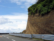 Race track - Right turn. Road on Oshima Island - Japan with strange vulcanic layered rock formation on the coast. It resembles a race track in computer games Royalty Free Stock Photo