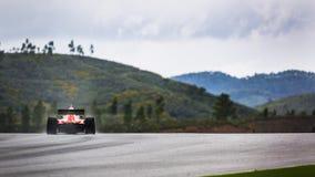 Raceauto in landschap van heuvels met nevel van regen Stock Afbeeldingen