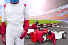 Raceautobestuurder het stellen voor het kuileinde met teammainta stock foto's