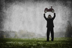 Racecar driver holding toy car. A racecardriver holding his toy car on top of his head Stock Photography