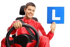 Racer in a car seat holding a learner plate royalty free stock photos