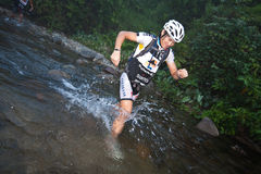 Racer makes his way across a river in the morning Stock Photography