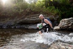 Racer makes  way across a river in the morning Stock Photos
