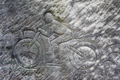 Racer on a motorbike - old rock relief Stock Photography