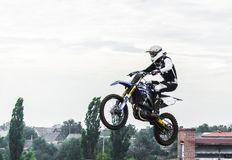The racer on a motorcycle participates in a motocross race, jumps on a springboard. Royalty Free Stock Photo