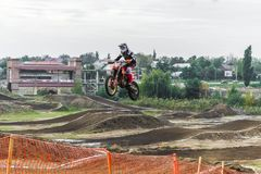 The racer on a motorcycle participates in a motocross race, jumps on a springboard. Royalty Free Stock Image