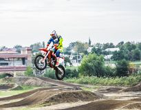 The racer on a motorcycle participates in a motocross race, jumps on a springboard. He took off high on a motorcycle. Royalty Free Stock Photo
