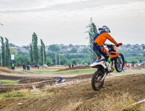 The racer on a motorcycle participates in a motocross race, takes off and jumps on a hill. Close-up. Extreme sports Stock Images