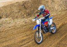 The racer on a motorcycle participates in race motocrosses, goes on sand. Red blue suit. Close-up. The racer on a motorcycle participates in race motocrosses stock photography