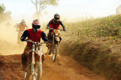 Racer motorcycle race. Racer compete in motorcycle race, motorcyclist try to speed up goal, red soil way, indistinct dust stock image