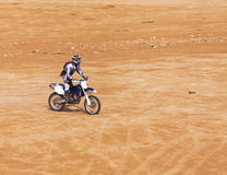 Racer on a motorcycle ride through the desert. In the summer Royalty Free Stock Image