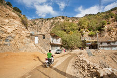 Racer on motorcycle rides through the mountain village on dirt road in Kurdistan Stock Images