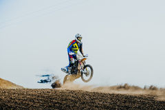 Racer on a motorcycle rides on rear wheel on a dusty track Royalty Free Stock Image