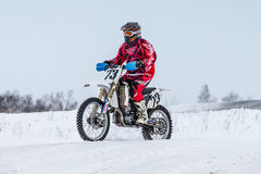 Racer on a motorcycle rides through snowy road race motocross Stock Photo
