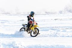 Racer on a motorcycle rides in turn of wheels a spray of snow Royalty Free Stock Photo
