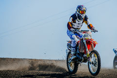 Racer motorcyclist riding on track under wheels of dirt Stock Image