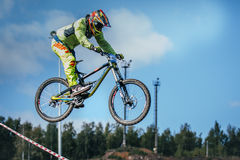 Racer on the mountain bike during the jump of the ski jumping against the sky Stock Photography