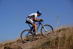 Racer mountain bike uphill against the sky Royalty Free Stock Photos