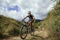 Racer mountainbiker rides on a mountain trail, smile on face Royalty Free Stock Photo