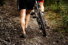 Racer mountainbiker walks mountain next to bike Stock Photos