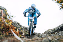 Racer mountianeer coming down a steep stone slope. Magnitogorsk, Russia - September 12, 2015: Athlete on a mountain bike is flying in a jump from a springboard royalty free stock image