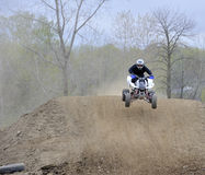 Racer Rides an ATV Down a Dirt Hill Stock Photos