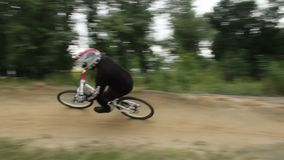 Racer rides BMX bicycle in helmet at competition circuit daytime. Stock footage stock video footage