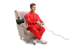 Racer sitting in an armchair and playing video games Stock Image