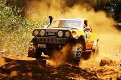 Racer at terrain racing car competition. The car try to cross extreme off road with red earth,  wheel make splash of soil and dusty air, competitor  adventure Royalty Free Stock Image