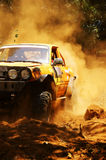 Racer at terrain racing car competition. The car try to cross extreme off road with red earth,  wheel make splash of soil and dusty air, competitor  adventure Royalty Free Stock Photos