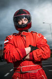 Racer wearing red racing protective suit and helmet royalty free stock photo