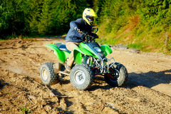 Racer with yellow helmet on green quad enjoying his ride outdoors. Royalty Free Stock Photo
