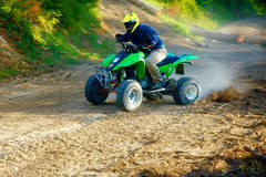 Racer with yellow helmet on green quad enjoying his ride outdoors. Royalty Free Stock Photos