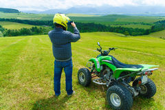 Racer with yellow helmet on green quad enjoying his ride outdoors. Royalty Free Stock Image