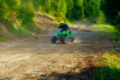 Racer with yellow helmet on green quad enjoying his ride outdoors. Stock Photography