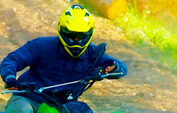 Racer with yellow helmet on green quad enjoying his ride outdoors. graphic version. Stock Photos