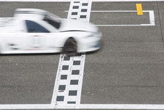 Racerbil som korsar mållinjen Royaltyfria Bilder