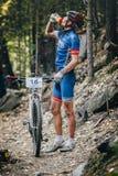 Racerbilcyklisten i trän som dricker sportar, dricker ut ur flaskan Arkivfoton