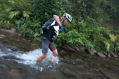A racermakes his way across a river in the morning Stock Photo
