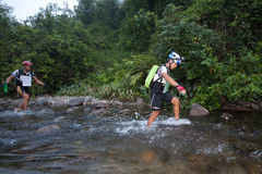 Racers makes  way across a river in the morning Stock Image