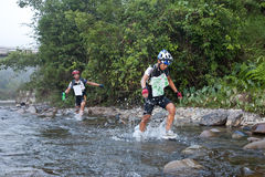 Racers makes  way across a river in the morning Stock Photo